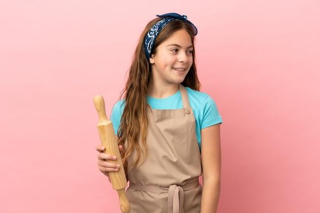 Menina caucasiana segurando um rolo de massa isolado no fundo rosa, olhando para o lado e sorrindo