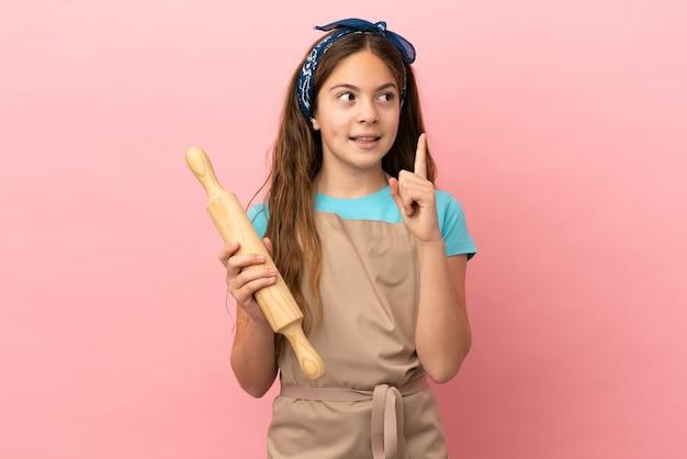 Menina caucasiana segurando um rolo de massa isolado no fundo rosa, pensando em uma ideia apontando o dedo para cima