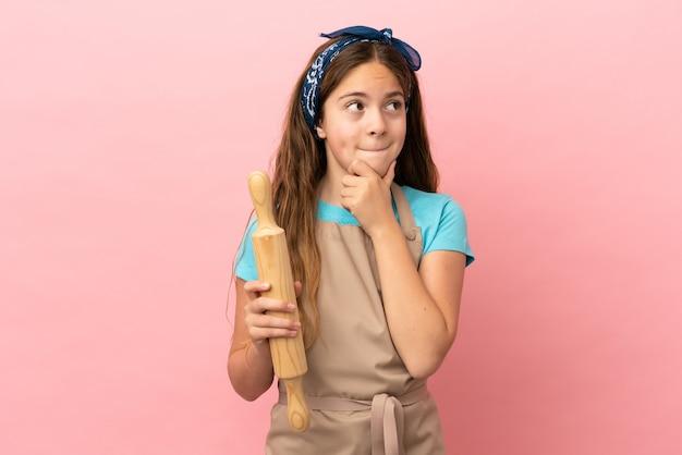 Menina caucasiana segurando um rolo de massa isolado no fundo rosa, tendo dúvidas e pensando