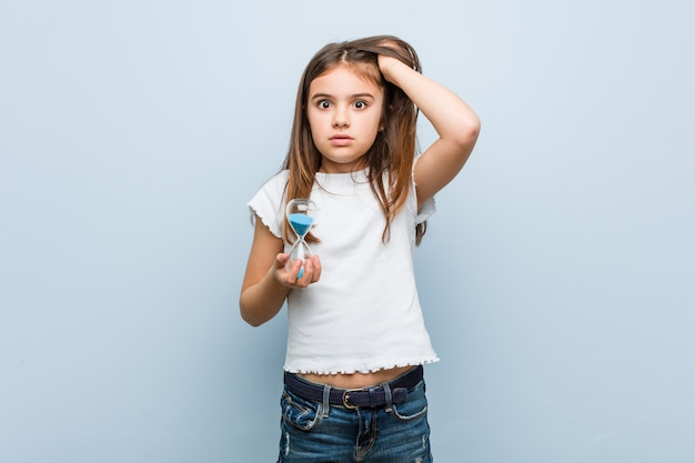 Menina caucasiana segurando uma ampulheta sendo chocado