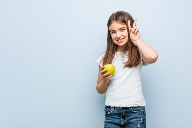 Menina caucasiana segurando uma maçã verde, mostrando sinal de vitória e sorrindo amplamente.