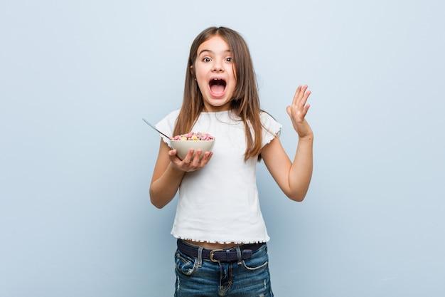 Menina caucasiana segurando uma tigela de cereais comemorando uma vitória ou sucesso