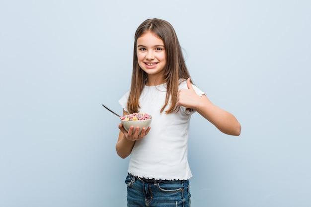 Menina caucasiana segurando uma tigela de cereais, sorrindo e levantando o polegar
