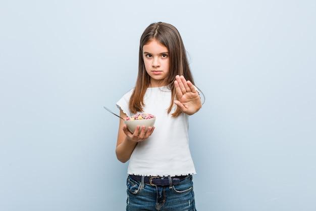 Menina caucasiana segurando uma tigela de cereal em pé com a mão estendida, mostrando o sinal de stop, impedindo-o.