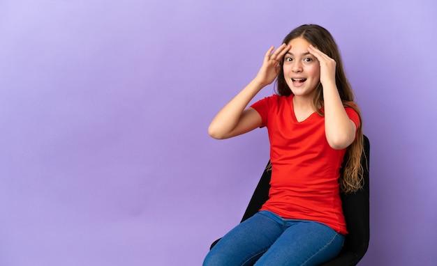 Menina caucasiana sentada em uma cadeira isolada em um fundo roxo com expressão de surpresa
