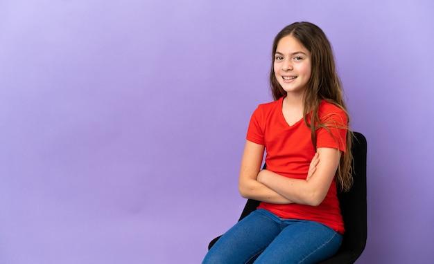 Menina caucasiana sentada em uma cadeira isolada em um fundo roxo com os braços cruzados e olhando para a frente