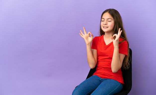 Menina caucasiana sentada em uma cadeira isolada em um fundo roxo em pose zen