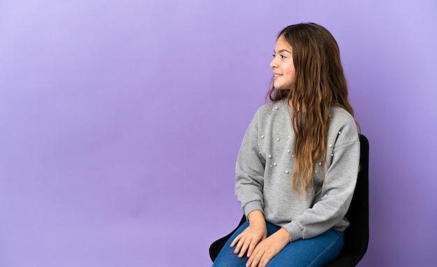 Menina caucasiana sentada em uma cadeira isolada em um fundo roxo na posição lateral
