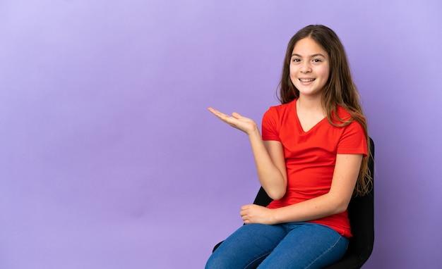 Menina caucasiana sentada em uma cadeira isolada em um fundo roxo, segurando o imaginário de copyspace na palma da mão para inserir um anúncio