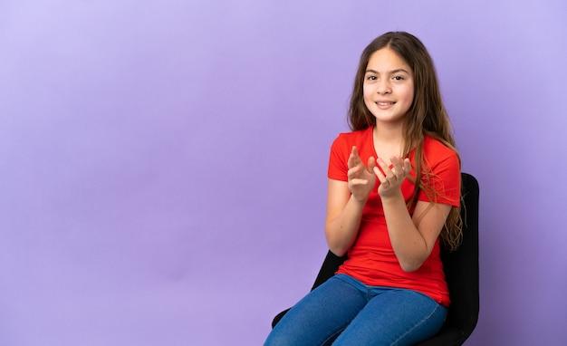 Menina caucasiana sentada em uma cadeira isolada no fundo roxo aplaudindo após apresentação em uma conferência