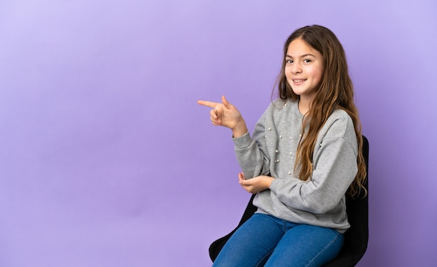Menina caucasiana sentada em uma cadeira isolada no fundo roxo apontando o dedo para o lado