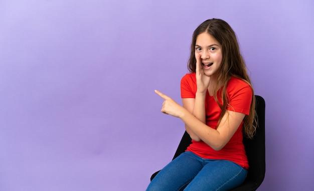 Menina caucasiana sentada em uma cadeira isolada no fundo roxo apontando para o lado para apresentar um produto e sussurrando algo