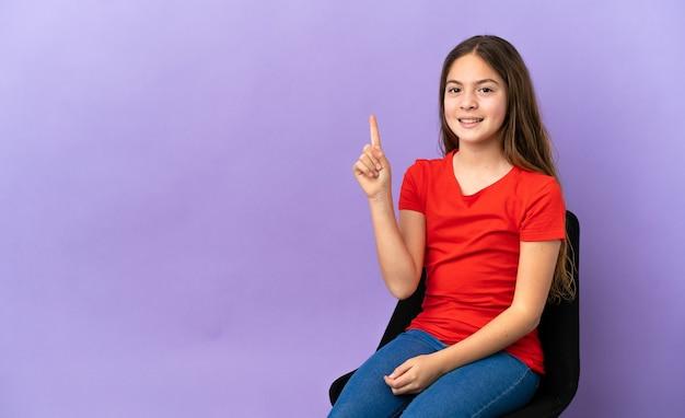 Menina caucasiana sentada em uma cadeira isolada no fundo roxo apontando para uma ótima ideia