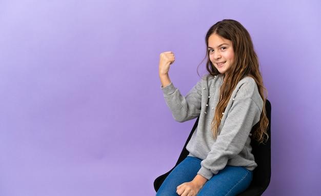Menina caucasiana sentada em uma cadeira isolada no fundo roxo comemorando uma vitória