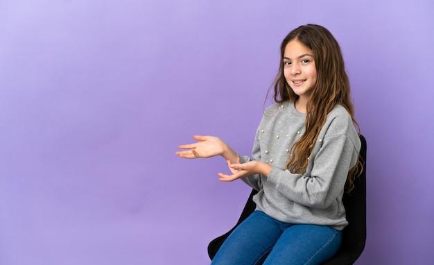 Menina caucasiana sentada em uma cadeira isolada no fundo roxo, estendendo as mãos para o lado para convidar para vir