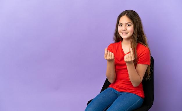 Menina caucasiana sentada em uma cadeira isolada no fundo roxo fazendo gesto de dinheiro