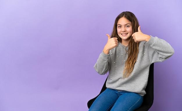 Menina caucasiana sentada em uma cadeira isolada no fundo roxo fazendo um gesto de polegar para cima