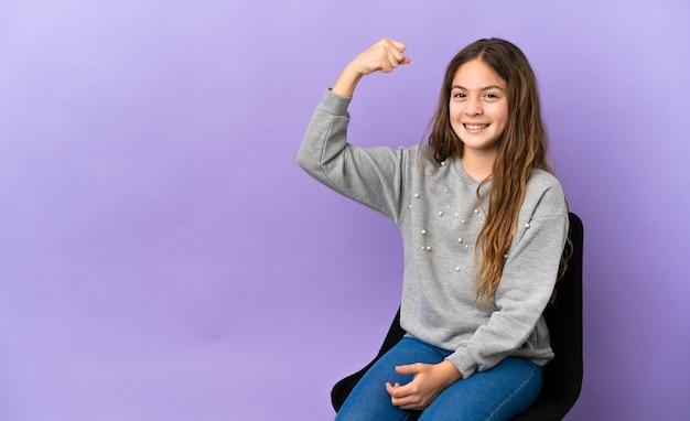 Menina caucasiana sentada em uma cadeira isolada no fundo roxo fazendo um gesto forte