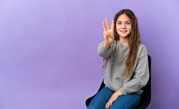 Menina caucasiana sentada em uma cadeira isolada no fundo roxo feliz e contando três com os dedos