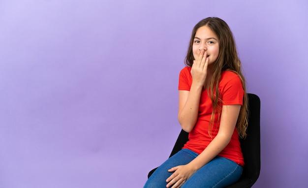 Menina caucasiana sentada em uma cadeira isolada no fundo roxo feliz e sorridente cobrindo a boca com a mão