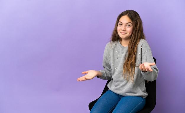 Menina caucasiana sentada em uma cadeira isolada no fundo roxo feliz e sorridente