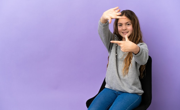 Menina caucasiana sentada em uma cadeira isolada no fundo roxo focalizando o rosto. símbolo de enquadramento