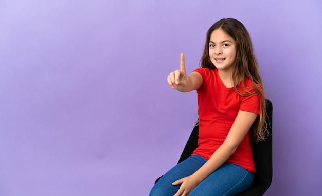 Menina caucasiana sentada em uma cadeira isolada no fundo roxo, mostrando e levantando um dedo