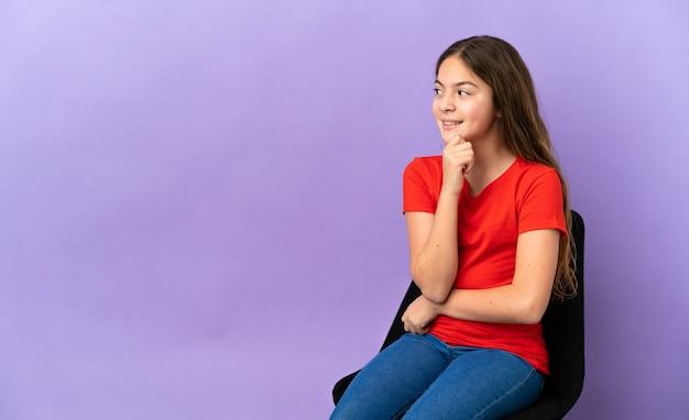 Menina caucasiana sentada em uma cadeira isolada no fundo roxo, pensando em uma ideia enquanto olha para cima