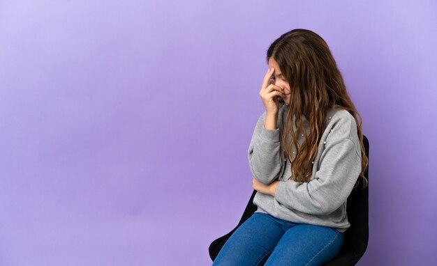 Menina caucasiana sentada em uma cadeira isolada no fundo roxo rindo