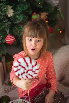 Menina caucasiana, sentado perto de árvore de natal e detém doces de brinquedo nas mãos e surpreso.