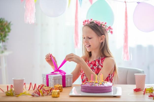 Menina caucasiana sonhadora sorrindo e olhando para o bolo de arco-íris de aniversário. fundo colorido festivo com balões. conceito de festa e desejos de aniversário.