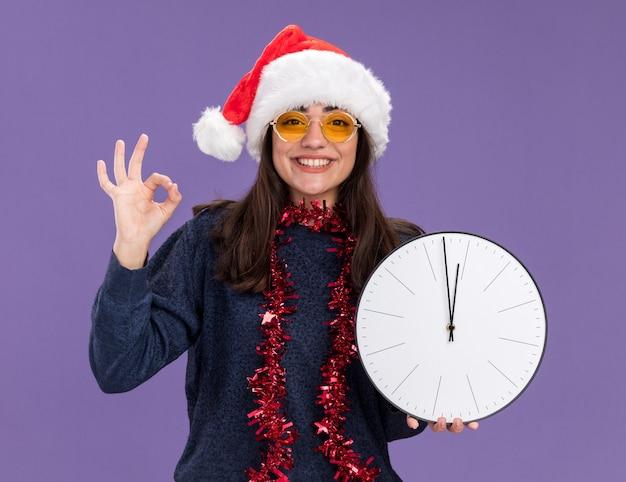 Menina caucasiana sorridente de óculos de sol com chapéu de papai noel e guirlanda no pescoço segurando relógio e gestos sinal de ok isolado na parede roxa com espaço de cópia
