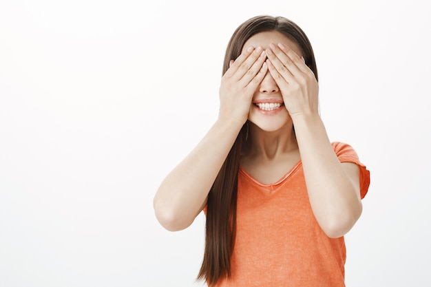 Menina caucasiana sorridente e ansiosa fechando os olhos e contando dez, esperando a surpresa