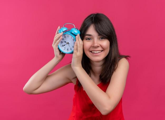 Menina caucasiana sorridente segurando o relógio com as duas mãos e olhando para a câmera em um fundo rosa isolado