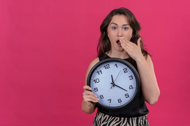 Menina caucasiana surpresa, vestindo camiseta preta, segurando um relógio de parede e colocando a mão na boca sobre um fundo rosa