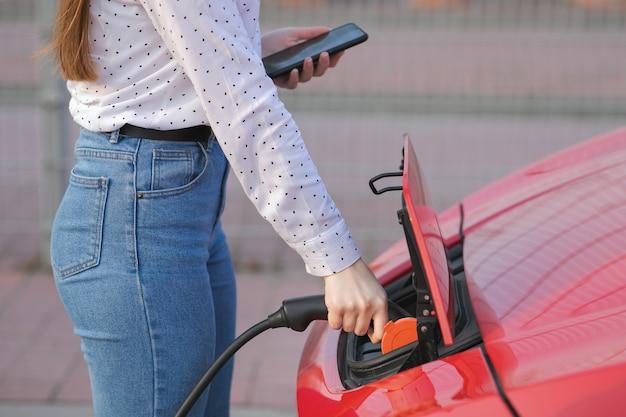 Menina caucasiana, usando telefone inteligente e fonte de alimentação à espera de conectar-se a veículos elétricos. processo de recarga elétrica do carro chega ao fim.