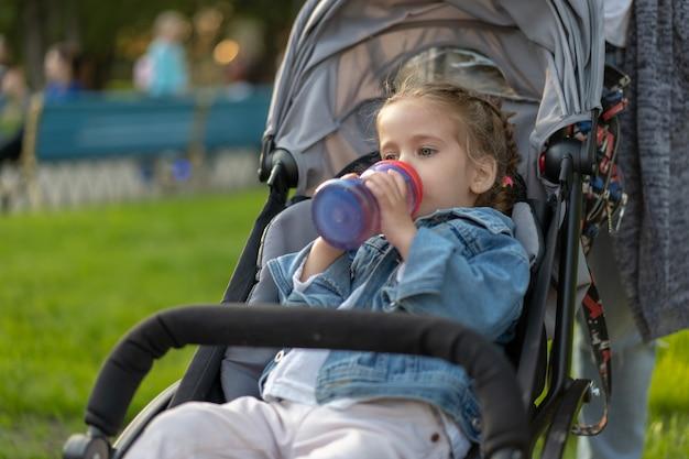 Menina caucasiana vestida com uma jaqueta jeans bebe suco de sua garrafa enquanto está sentado em um carrinho de bebê