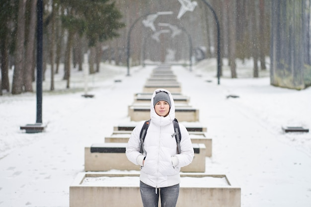 Menina caucasiana, vestida de jaqueta branca, desfrutando de neve no parque