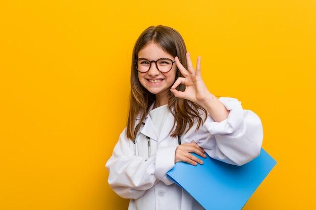 Menina caucasiana vestindo um traje de médico alegre e confiante mostrando okey gesto.