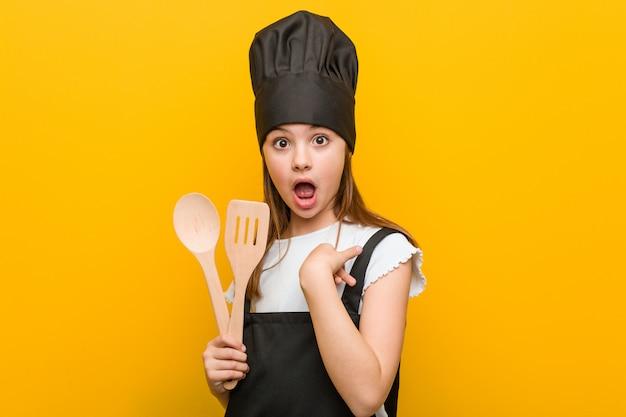 Menina caucasiana, vestindo uma fantasia de chef surpreendeu apontando para si mesmo, sorrindo amplamente.