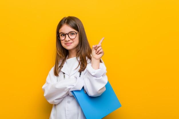 Menina caucasiana vestindo uma fantasia de médico, sorrindo alegremente, apontando com o dedo indicador para longe.