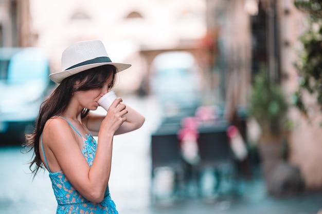 Menina caucasiano beber café quente bebida andando na rua na europa