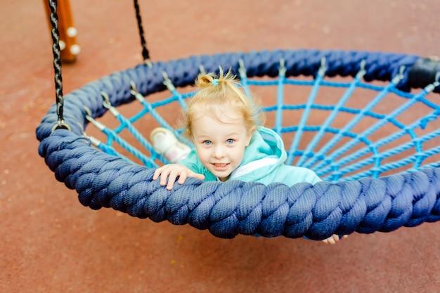 Menina caucasiano bonito da criança 4 anos velha tendo o divertimento em uma corrediça em um campo de jogos no dia de verão.