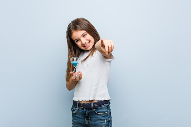 Menina caucasiano pequena que guarda sorrisos alegres de uma ampulheta que apontam para frontear.