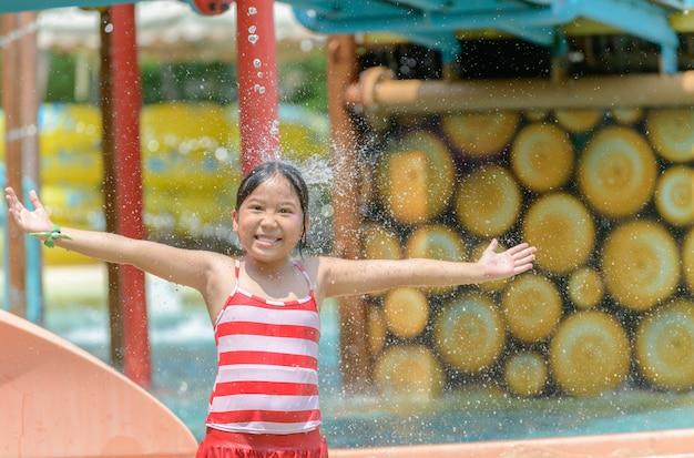 Menina caucasiano pouco feliz jogando água no parque aquático