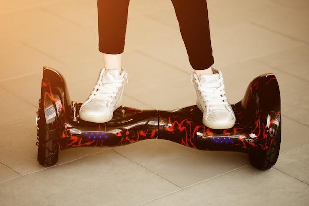 Menina cavalga no giroscópio. pernas de criança em tênis on mini segway