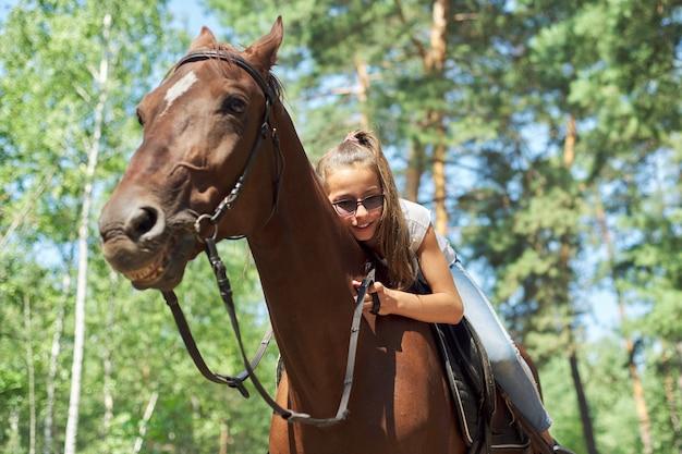 Menina, cavalgando, cavalo de verão, passeio na floresta, menina abraçou carinhosamente o cavalo.