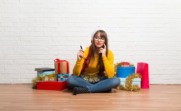 Menina, celebrando, a, natal, feriados, segurando, um, cartão crédito, e, pensando