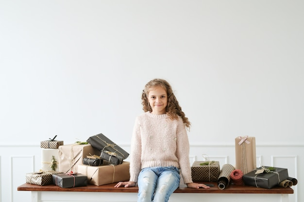 Menina cercada por caixas de presente