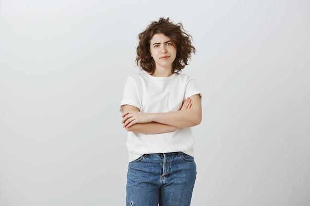 Menina cética descontente com os braços cruzados e parecendo crítica